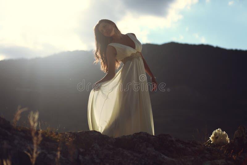 Belle femme sur le dessus de montagne dans la lumière de coucher du soleil photos stock
