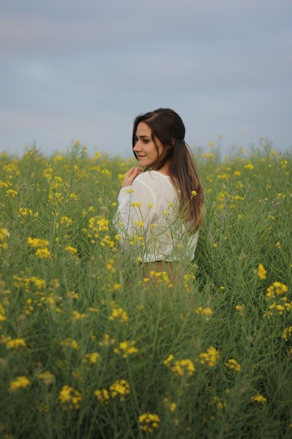 Belle femme sur le gisement de fleurs jaune avec le ciel nuageux foncé images libres de droits