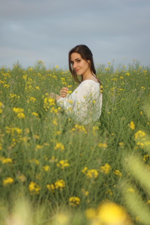 Belle femme sur le gisement de fleurs jaune avec le ciel nuageux foncé image stock