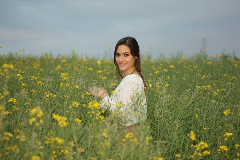 Belle femme sur le gisement de fleurs jaune avec le ciel nuageux foncé images stock