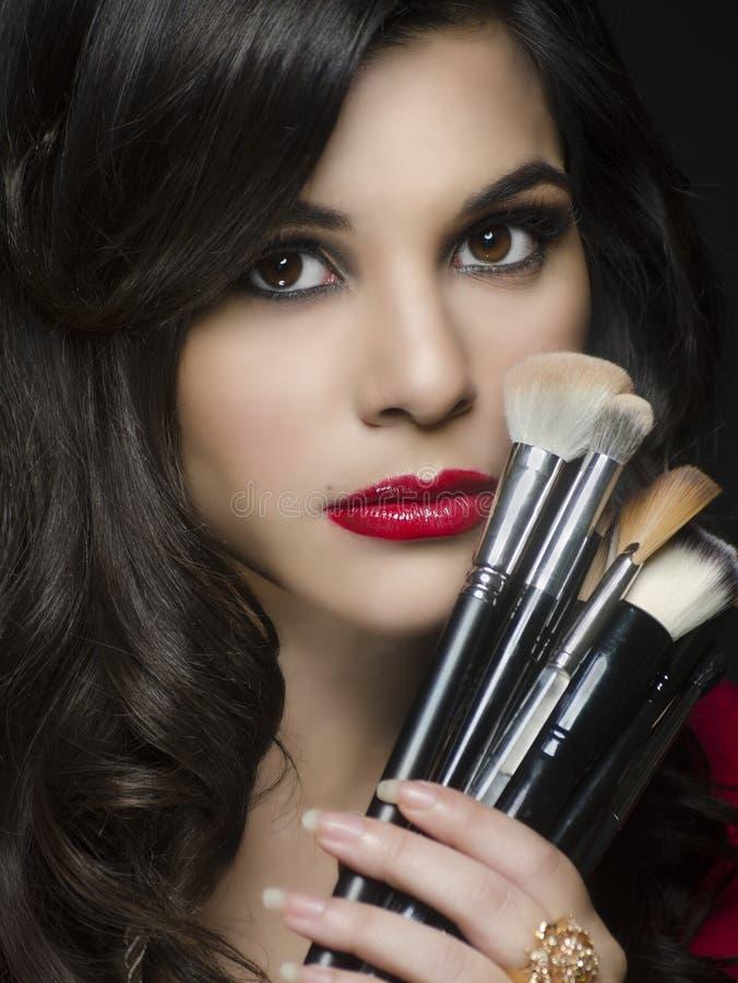 Belle femme tenant des brosses de maquillage images libres de droits