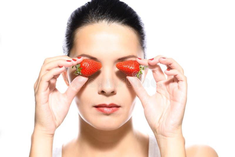 Belle femme tenant des fraises sur ses yeux photographie stock