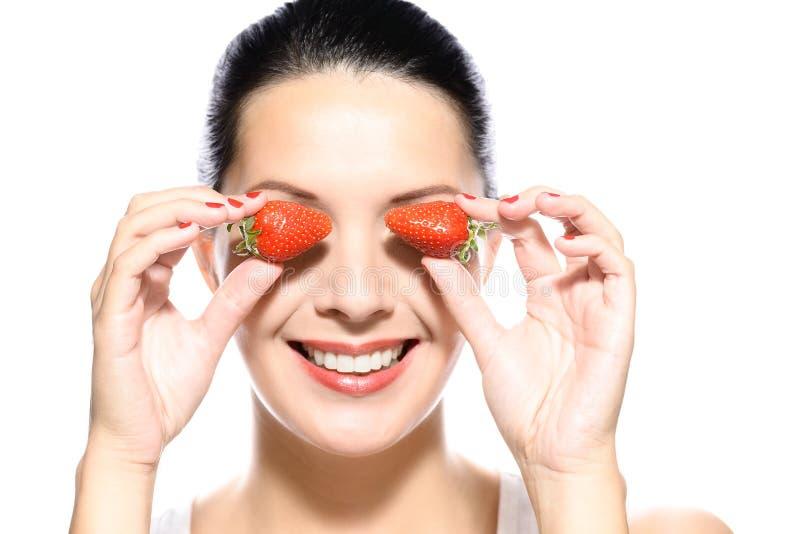 Belle femme tenant des fraises sur ses yeux images stock