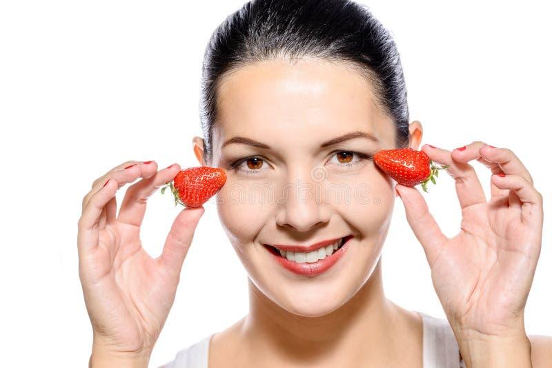 Belle femme tenant des fraises sur ses yeux photographie stock libre de droits