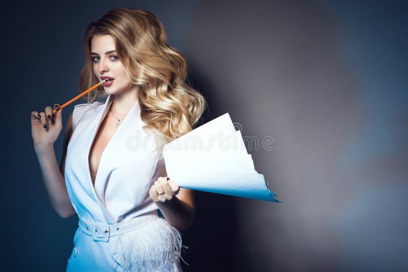 Belle femme tenant des papiers et mordant le bord du crayon par espièglerie photos stock