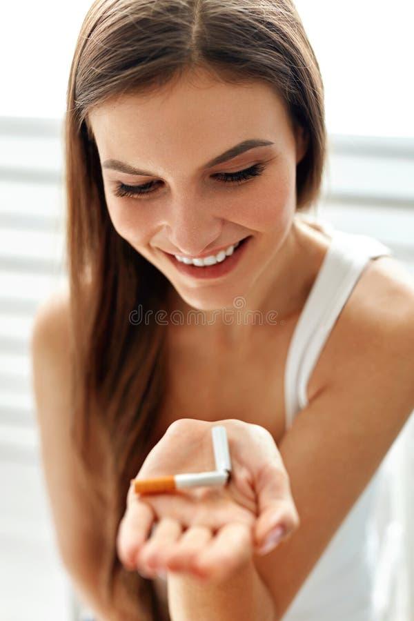 Belle femme tenant la cigarette cassée Abandon des cigarettes photographie stock