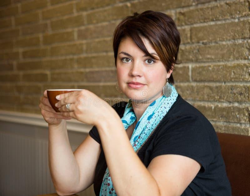 Belle femme tenant la tasse de café en café images libres de droits