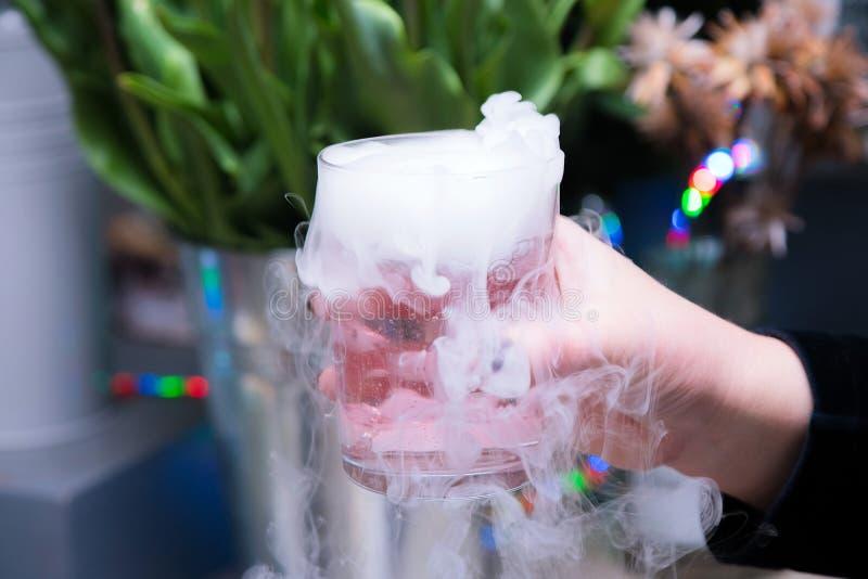 Belle femme tenant le cocktail de glace carbonique à la partie Boisson pourpre de cocktail avec de la vapeur de glace au club photographie stock