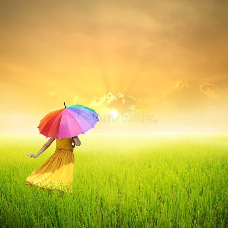 Belle femme tenant le parapluie dans le domaine et le coucher du soleil d'herbe verte photographie stock