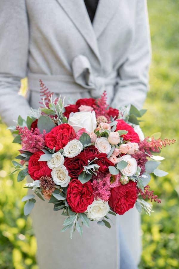 Belle femme tenant un beau bouquet de mariage d'automne composition florale avec les roses blanches et rouges de jardin Pelouse v photo libre de droits