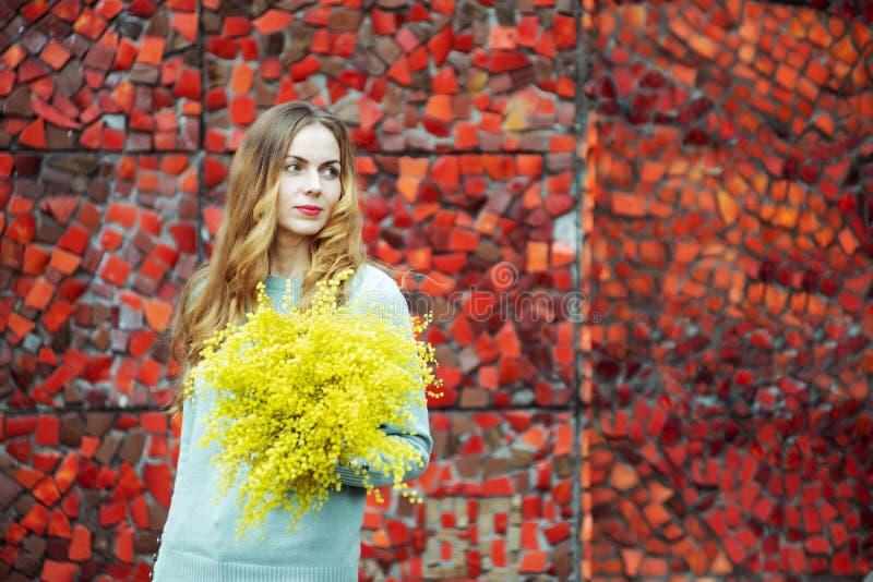 Belle femme tenant un bouquet de la mimosa, portrait sur un fond rouge lumineux photographie stock