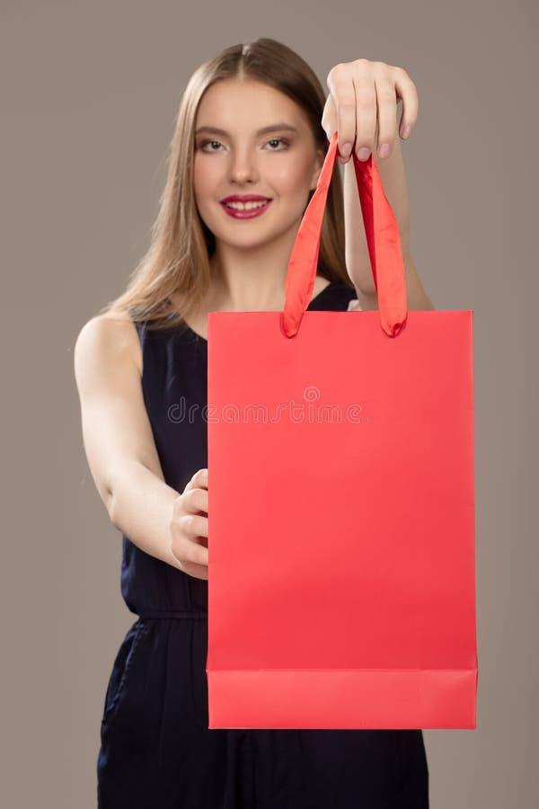 Belle femme tenant un paquet rouge Façonnez le sourire de femme photo libre de droits