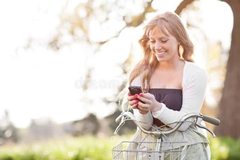 Belle femme texting à son téléphone extérieur image stock