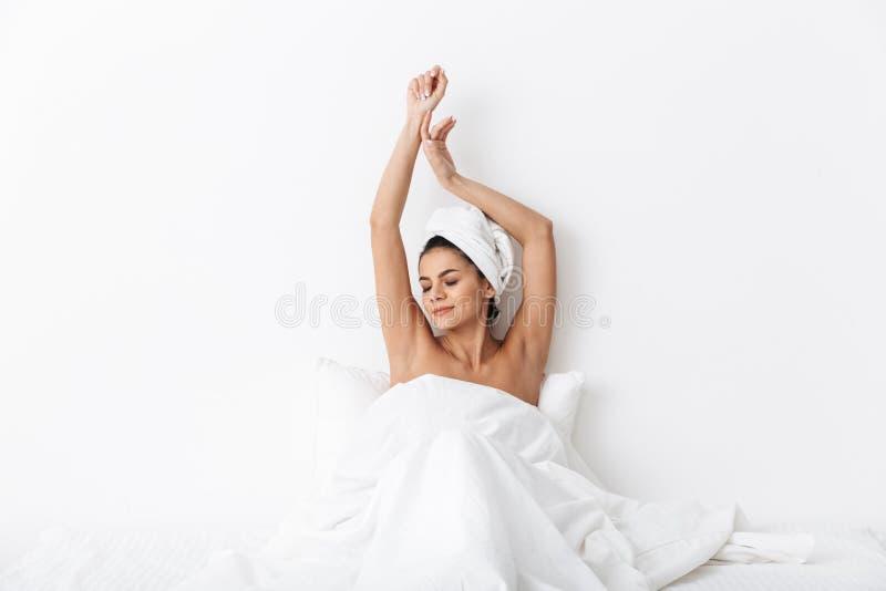 Belle femme ?tonnante avec la serviette sur les mensonges principaux dans le lit sous la couverture d'isolement au-dessus du fond photo libre de droits
