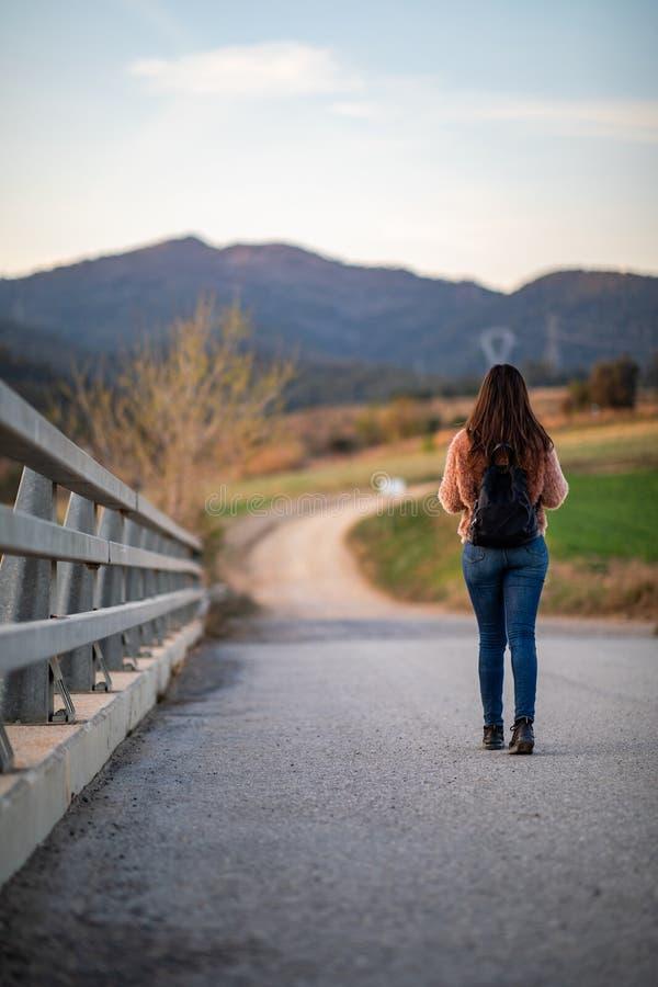 Belle femme trimardant au-dessus d'un pont avec le chemin et les montagnes brouillés sur le fond photo stock