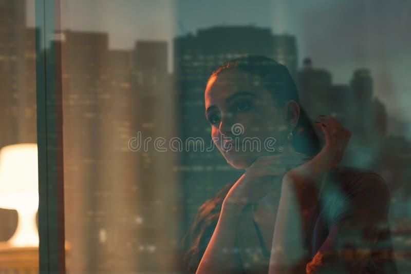Belle femme triste s'asseyant à côté d'une fenêtre image stock