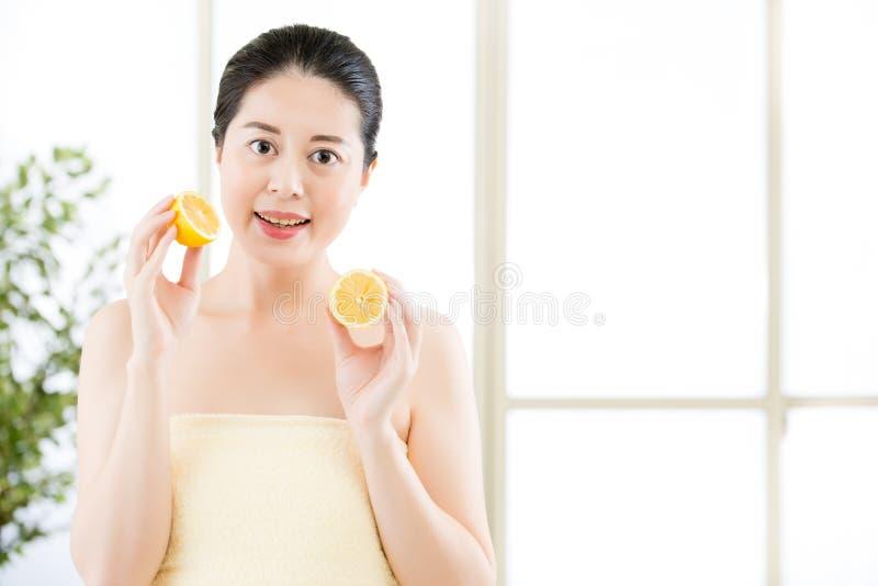 Belle fette asiatiche della tenuta della donna di limone Bellezza sana immagine stock