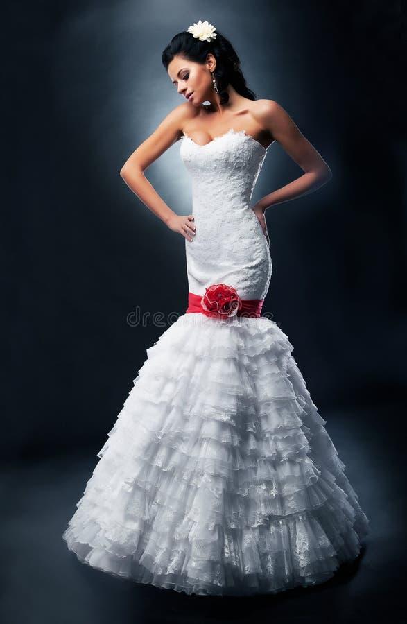 Belle fiancée dans la robe nuptiale avec la proue rouge photos stock