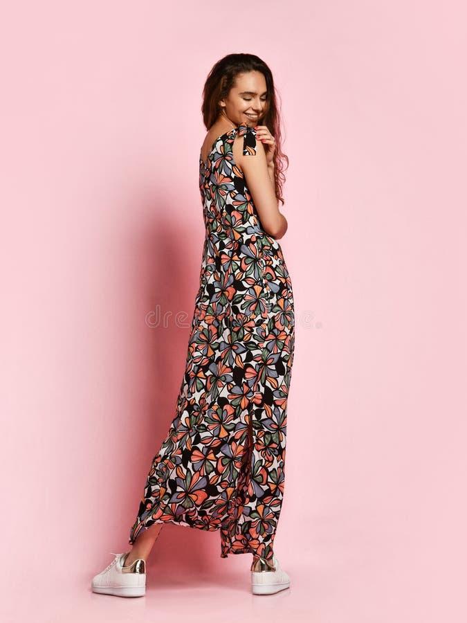 Belle fille à la mode de brune dans une longue robe fleurie au plancher et aux espadrilles posant sur un fond rose image libre de droits