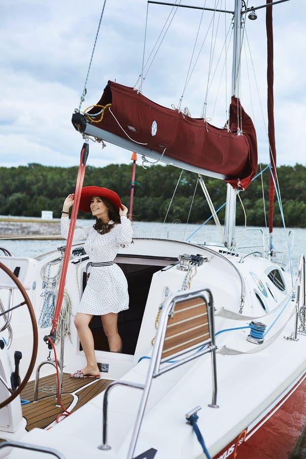 Belle fille à la mode de modèle de brune de ND dans la robe élégante courte blanche souriant, ajustement de son chapeau rouge à l images libres de droits