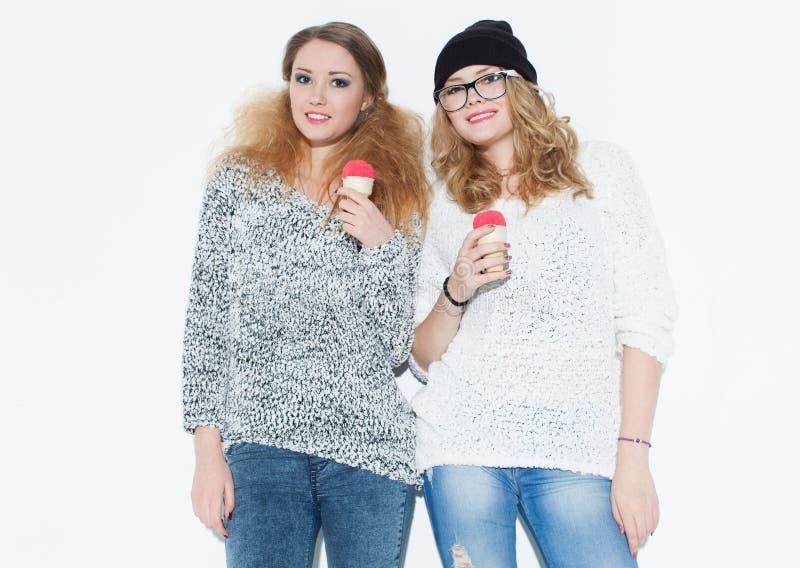Belle fille à la mode mangeant la crème glacée et amusement posant près d'un mur blanc d'intérieur studio image stock