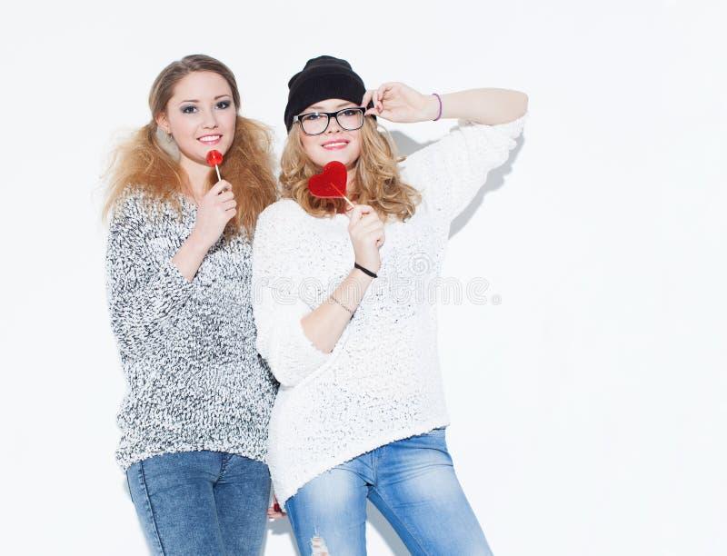 Belle fille à la mode mangeant la lucette et amusement posant près d'un mur blanc d'intérieur studio photo libre de droits
