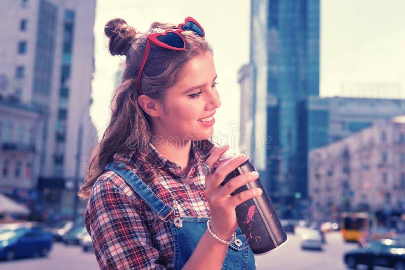 Belle fille à la mode moderne buvant la boisson régénératrice froide d'énergie images libres de droits