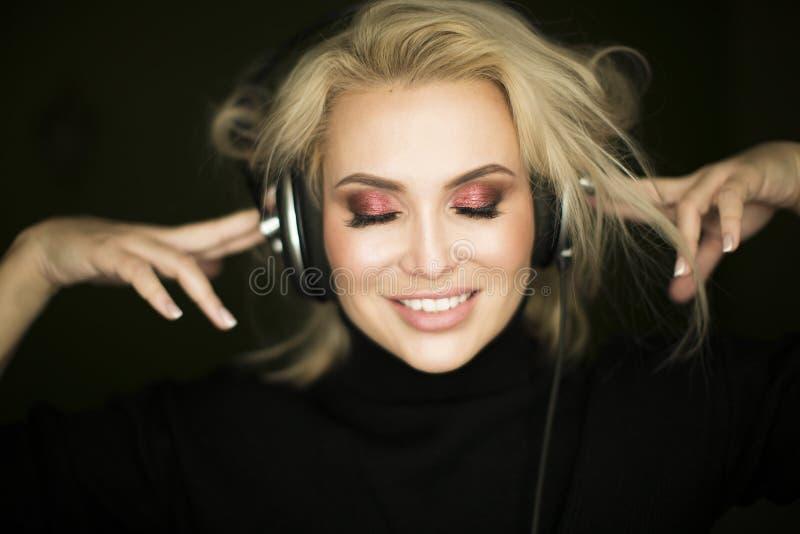 Belle fille écoutant la musique sur le fond foncé photos stock