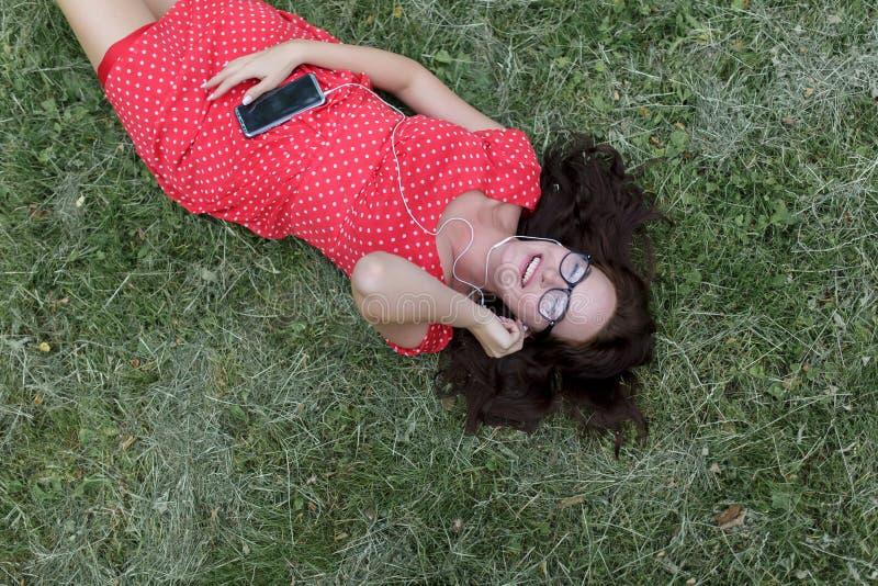 Belle fille écoutant la musique sur son smartphone se trouvant sur l'herbe Vue sup?rieure images libres de droits