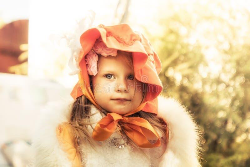 Belle fille élégante d'enfant dans le manteau avec le portrait d'extérieur de chapeau avec la lumière du soleil chaude sur l'enfa photos libres de droits