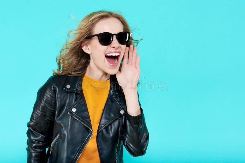 Belle fille élégante géniale de balancier dans la veste en cuir et des lunettes de soleil noires Le punk n'est pas mort Cris frai image libre de droits