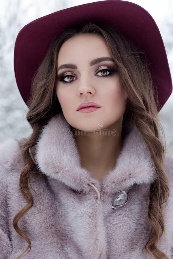Belle fille élégante mignonne dans un manteau de fourrure et un chapeau marchant le matin givré lumineux de forêt d'hiver photographie stock