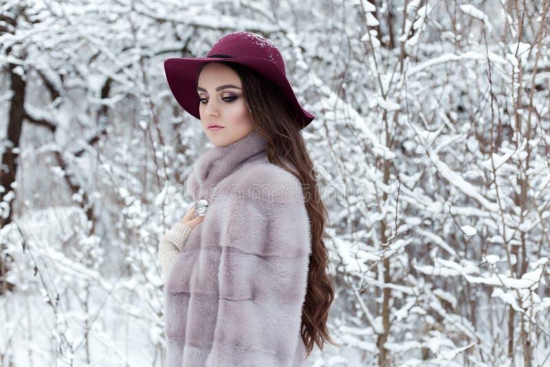 Belle fille élégante mignonne dans un manteau de fourrure et un chapeau marchant le matin givré lumineux de forêt d'hiver photographie stock libre de droits