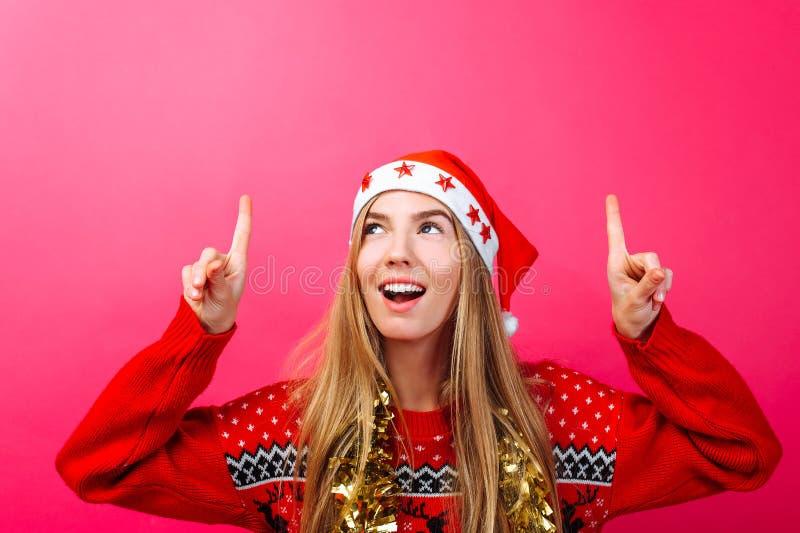 Belle fille étonnée dans le chapeau de Santa, avec la tresse sur son cou dirigeant des doigts et montrant un espace vide de copie image stock