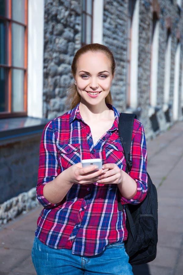 Belle fille adolescente d'étudiant avec le téléphone et le sac à dos photo libre de droits