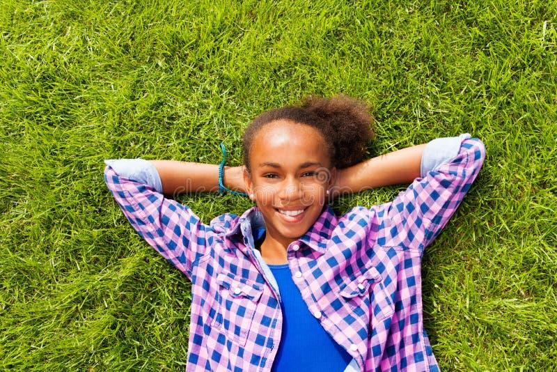 Belle fille africaine de sourire s'étendant sur l'herbe images stock