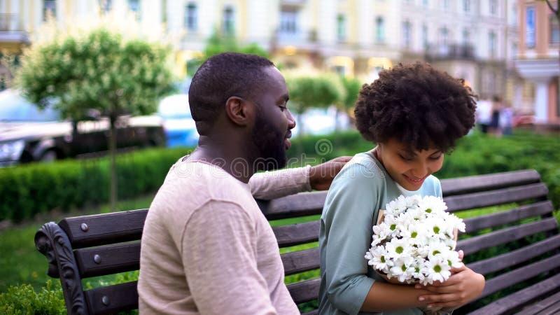 Belle fille africaine se sentant heureuse avec des fleurs la date, étreindre doux de couples photo libre de droits
