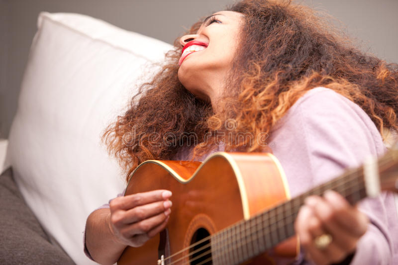 Belle fille afro-américaine jouant la guitare images libres de droits