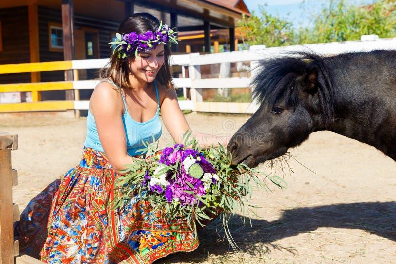 Belle fille alimentant le poney de paille à la ferme photos libres de droits