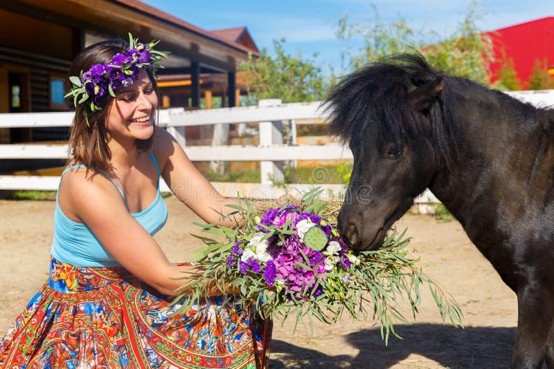 Belle fille alimentant le poney de paille à la ferme image libre de droits