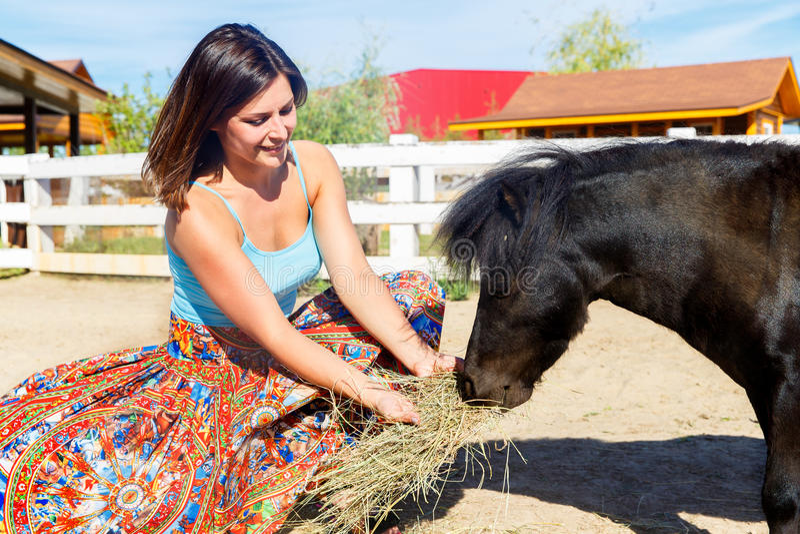 Belle fille alimentant le poney de paille à la ferme images libres de droits