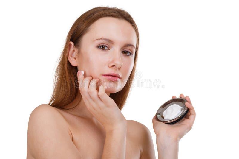 Belle fille appliquant la crème cosmétique sur le visage Le concept de la beauté D'isolement sur le blanc photographie stock libre de droits
