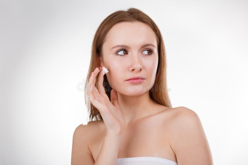 Belle fille appliquant une crème sur son visage Concept parfait de peau photographie stock