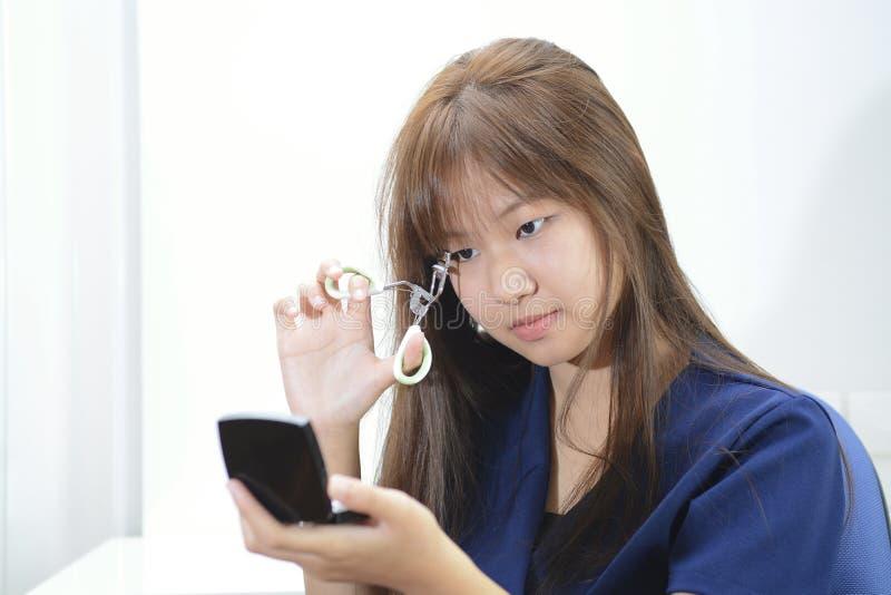 Belle fille asiatique à l'aide du bigoudi de cil image stock