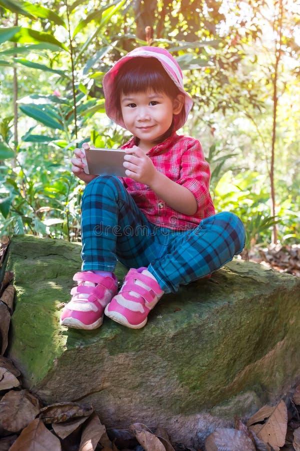 Belle fille asiatique à l'aide du téléphone intelligent sur le rocher au-dessus du backg de nature images libres de droits