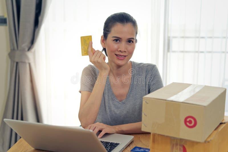 Belle fille asiatique achetant en ligne du site Web utilisant la carte de crédit pour le paiement photographie stock libre de droits
