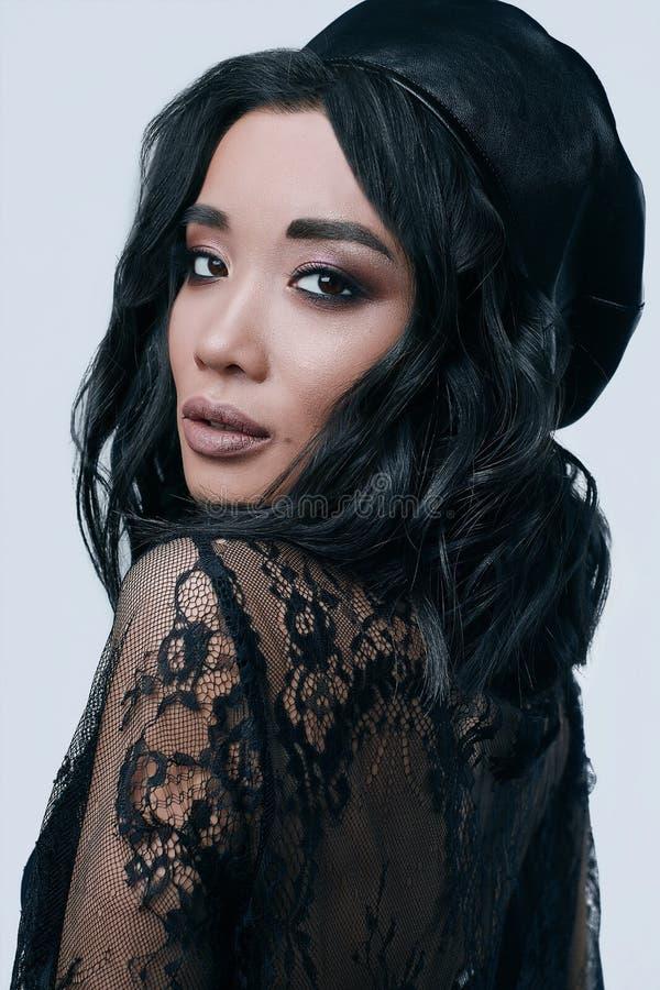 Belle fille asiatique avec du charme dans le long chapeau noir de robe et de cuir images libres de droits
