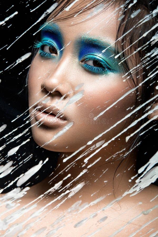 Belle fille asiatique avec le maquillage bleu lumineux images stock