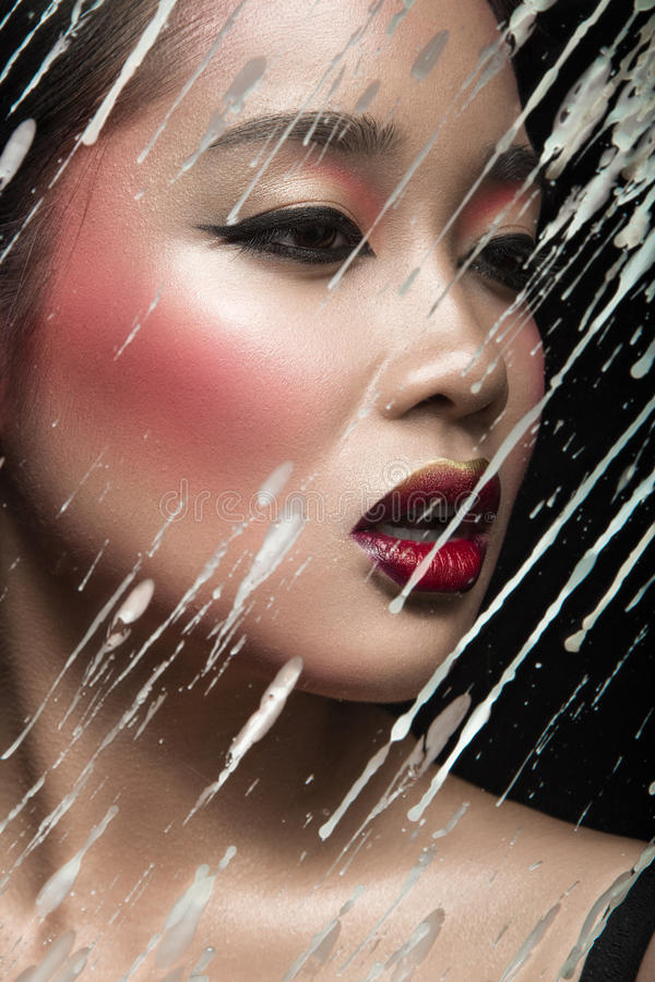 Belle fille asiatique avec le maquillage lumineux derrière photographie stock