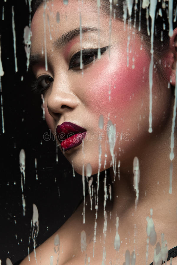 Belle fille asiatique avec le maquillage lumineux derrière le verre et les baisses de la cire Visage de beauté photo libre de droits